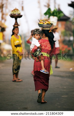 BALI, INDONESIA - JUNE 2: Balinese woman with cild loads the offering of food in wooden jar on her head for the ceremony in Ubud temple, Bali on June 2, 2014 - stock photo