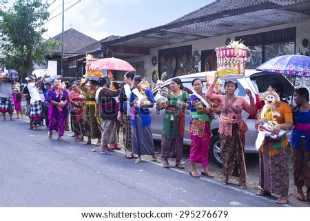 BALI, INDONESIA- JUNE 21, 2015: Cremation ceremony, village procession. Balinese people in traditional clothes and with donations walking along the road. - stock photo