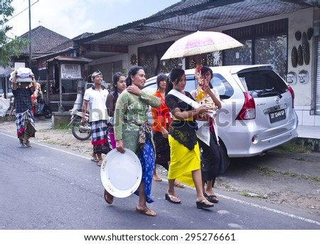 BALI, INDONESIA- JUNE 21, 2015: Part of cremation ceremony. Balinese women in traditional clothes and with donations walking along the road.  - stock photo