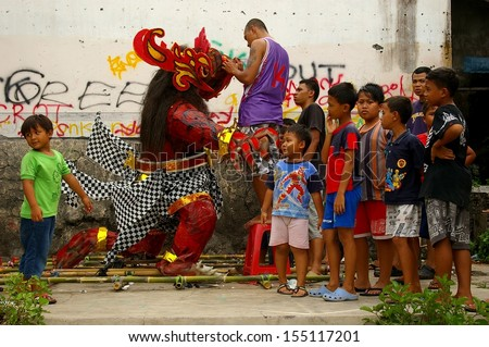 BALI, INDONESIA - MARCH 7: Unidentified boys with a monster statue for the Hindu festival Pengrupukan March 7, 2008 in Nusa Dua, Bali. This Celebrates the Balinese New Year and the arrival of spring.  - stock photo