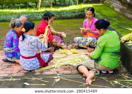 Bali, Indonesia, May 3, 2015. Balinese women make decorations of palm leaves for the feast at the local temple in Bali, Indonesia. Offering flowers and other gifts is very popular tradition on Bali.