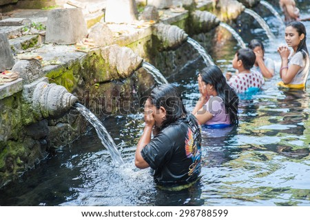 BALI, INDONESIA - NOVEMBER 3RD 2014 : Balinese people cleansing themselves in the Holy Spring at Tirtha Empul Bali, Indonesia. - stock photo