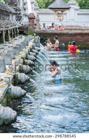 BALI, INDONESIA - NOVEMBER 3RD 2014 : Tourist cleansing themselves in the Holy Spring at Tirtha Empul Bali, Indonesia. - stock photo