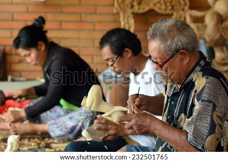 BALI, INDONESIA - NOVEMBER 12: Woodcarvers on November 12, 2014 in Bali, Indonesia. Woodcarving is very famous in some villages of Bali. - stock photo