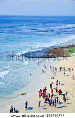 BALI, INDONESIA - OCT 18: Wide sand beach with tourists in sunny day on October 18, 2010. Dreamland beach, Bali, Indonesia. The Dreamland is one of the most popular surfing areas of Bali. - stock photo