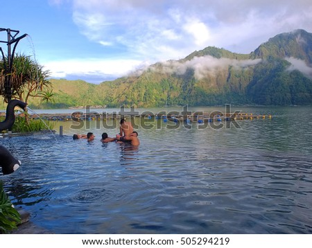 BALI, INDONESIA - OCTOBER 26, 2016: Unknown people bathing in a hot springs infinity pool beside Batur lake, Kintamani, Bali, Indonesia.