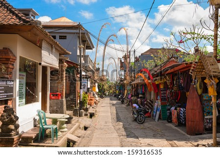 BALI, INDONESIA - SEP 19: Tourist street decorated by traditional penjor with shops and tours on Sep 19, 2012 in Ubud, Bali, Indonesia. Ubud is popular tourist attraction.  - stock photo