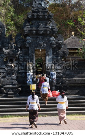 BALI, INDONESIA - SEP 26: Women with offers come in the temple gate for sacred ceremony in Goa Lawah Bat Cave on Sep 26, 2012 in Bali, Indonesia - stock photo
