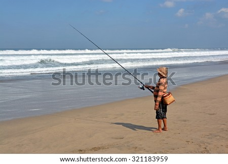 Bali, Indonesia - September 14, 2015: Balinese Fisherman Surf Casting on a summer day at  Legian Beach. - stock photo