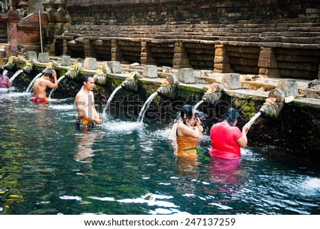 BALI, INDONESIA - SEPTEMBER 22: People washing themselves in the water Pura Tirta Empul temple, known by the sacred water purification. Bali, Indonesia, september 22, 2014 - stock photo