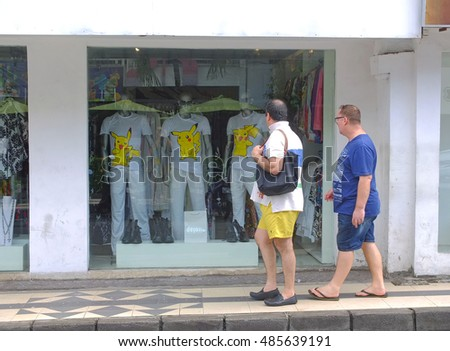 BALI, INDONESIA - SEPTEMBER 17, 2016: Tourists walking past store front with Pokemon t-shirts, Bali, Indonesia.