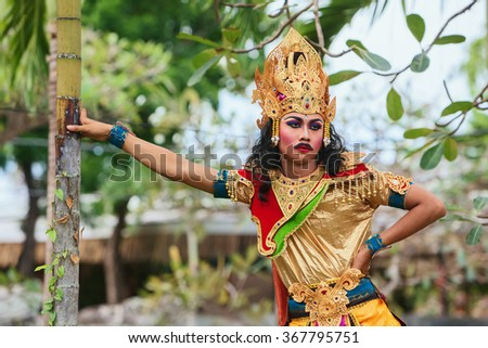 BALI ISLAND, INDONESIA - JUNE 20, 2015: Portrait of young man dressed in colorful ethnic Balinese people costume before dancing traditional ritual temple dance at Art and Culture Festival. - stock photo