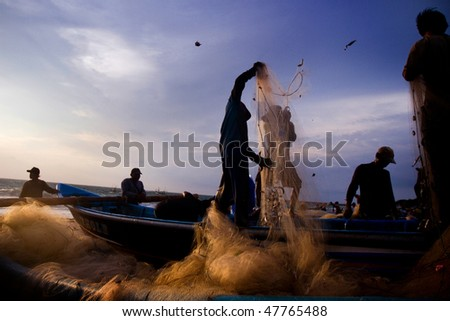 BALI - JANUARY 16: Life in a fishing village, fishermen release the fish from the net at dusk at Jimbaran village, Bali January 16, 2010 in Bali, Indonesia. - stock photo