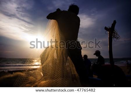 BALI - JANUARY 16: Life in a fishing village, fishermen repair nets at dusk at Jimbaran village, Bali January 16, 2010 in Bali, Indonesia. - stock photo