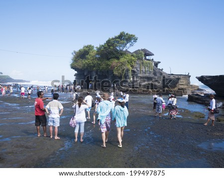 BALI - MAY 2014 : Tourists visit Tanah Lot in Bali, Indonesia on May 16, 2014. The home of a pilgrimage temple is a rock formation off Bali and a popular tourist and cultural icon for photography.