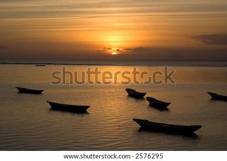 Bali sunset with fishing boats - stock photo