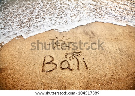 Bali title with sun and palm drawing on the sand beach near the ocean - stock photo