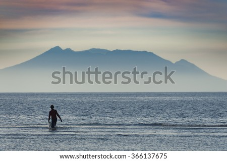 Balinese Seaweed Farmer. A seaweed collector in the village of Pemuteran, Bali. The island of Java can be seen in the background during a lovely sunrise. - stock photo