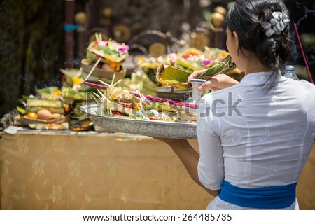 Balinese  woman carrying offering to local temple in Bali, Indonesia. Offering flowers and other gifts is very popular tradition on Bali. - stock photo