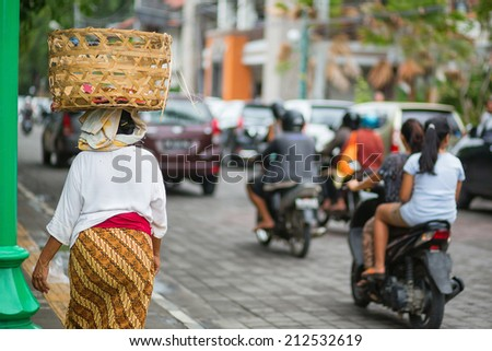 Balinese woman on a street of Ubud carrying basket on her head - stock photo
