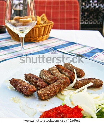 Balkan plate, cevapcici: grilled meatballs of different kind of meat mixed together with garlic, served with raw sliced onions and a red pepper (ajvar) dressing - stock photo