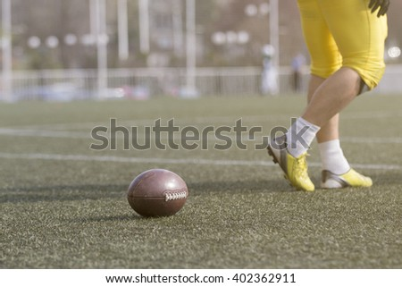 Ball and American football player on the field  - stock photo