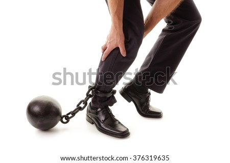 Ball and chain restraining a businessman as he tries to walk concept for business burden, willpower and determination - stock photo