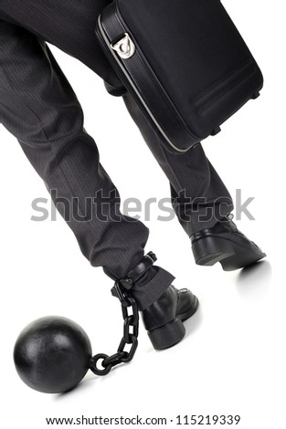 Ball and chain restraining a businessman as he walks away with a briefcase - stock photo