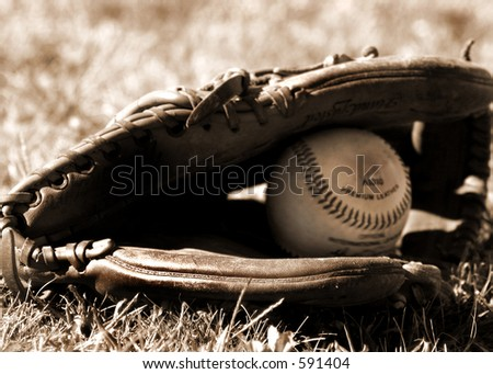 ball and glove in  the grass, sepia-toned - stock photo