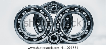 ball-bearings, gears in metal blue toning, set against a light background - stock photo