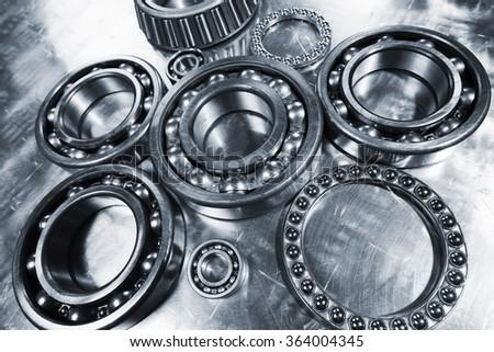 ball-bearings, pinions against brushed aluminum, titanium and steel aerospace parts - stock photo