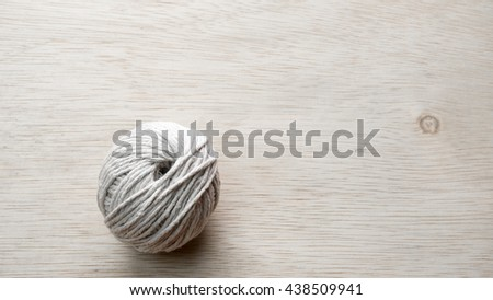 Ball of baumwolle yarn cotton wool on wooden floor surface. Slightly de-focused and close-up shot. Copy space. - stock photo