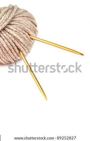 Ball of beige cotton yarn and knitting needles isolated on white background