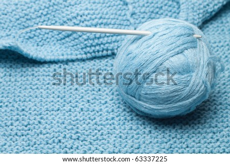 ball of blue wool with grey knitting needle