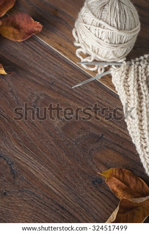 Ball of gray yarn and knitting on wood brown  table - stock photo