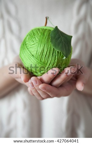 Ball of green wool in the form of an apple. Green apple of woolen thread. Hands holding a ball of wool. Light background. Knitted Sweater White. - stock photo
