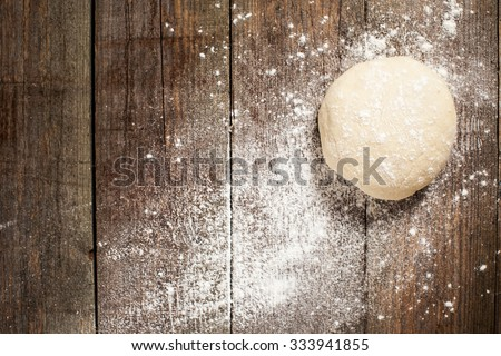 Ball of pizza dough on a rustic wooden background with dusting of flour - stock photo