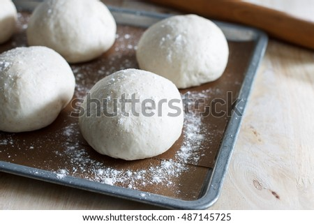 ball of pizza dough or bread dough on baking sheet paper with rolling.