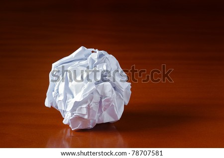 Ball of smashed sheet of paper over wooden table - stock photo