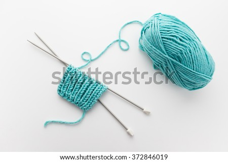 Ball of Yarn and Knitting Needles (fisherman's rib knitting pattern) - stock photo