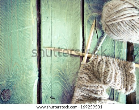 Ball of yarn and knitting on a wooden table. Retro style - stock photo