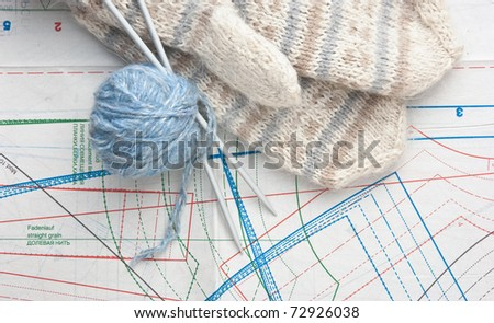 ball of yarn and mittens on a background pattern - stock photo