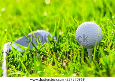 ball on a stand and a golf club - stock photo