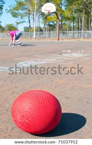 ball on playground with giirl writing chalk - stock photo
