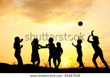 Ball playing happy children on meadow, sunset, summertime - stock photo