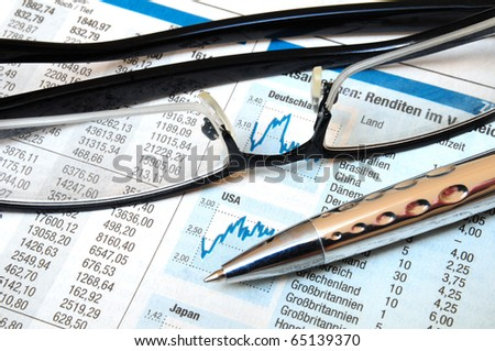 Ball point and glasses on top of a stock exchange report