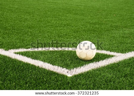 Ball prepared for corner kick. Heated football playground. corner on artificial green turf ground with painted white line marks. Milled black rubber in basic. - stock photo