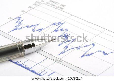 Ballboint pen on stock chart--focus on the tip of the ballpoint pen. - stock photo