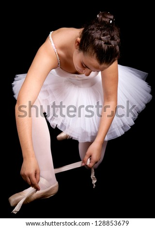 Ballerina dancer tiding up her shoe laces on black background - stock photo