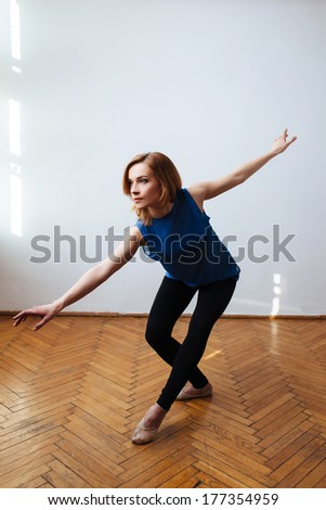 Ballerina in a training stretching her arms - stock photo